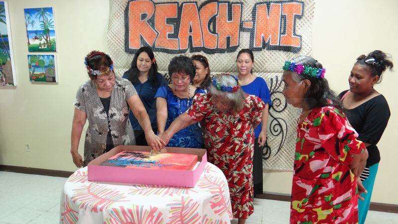 Maria Capital (left) and Lemeyo Abon (right) joined REACH-MI President Rosania Bennett to cut the cake officially launching the new organization. Photo: Giff Johnson